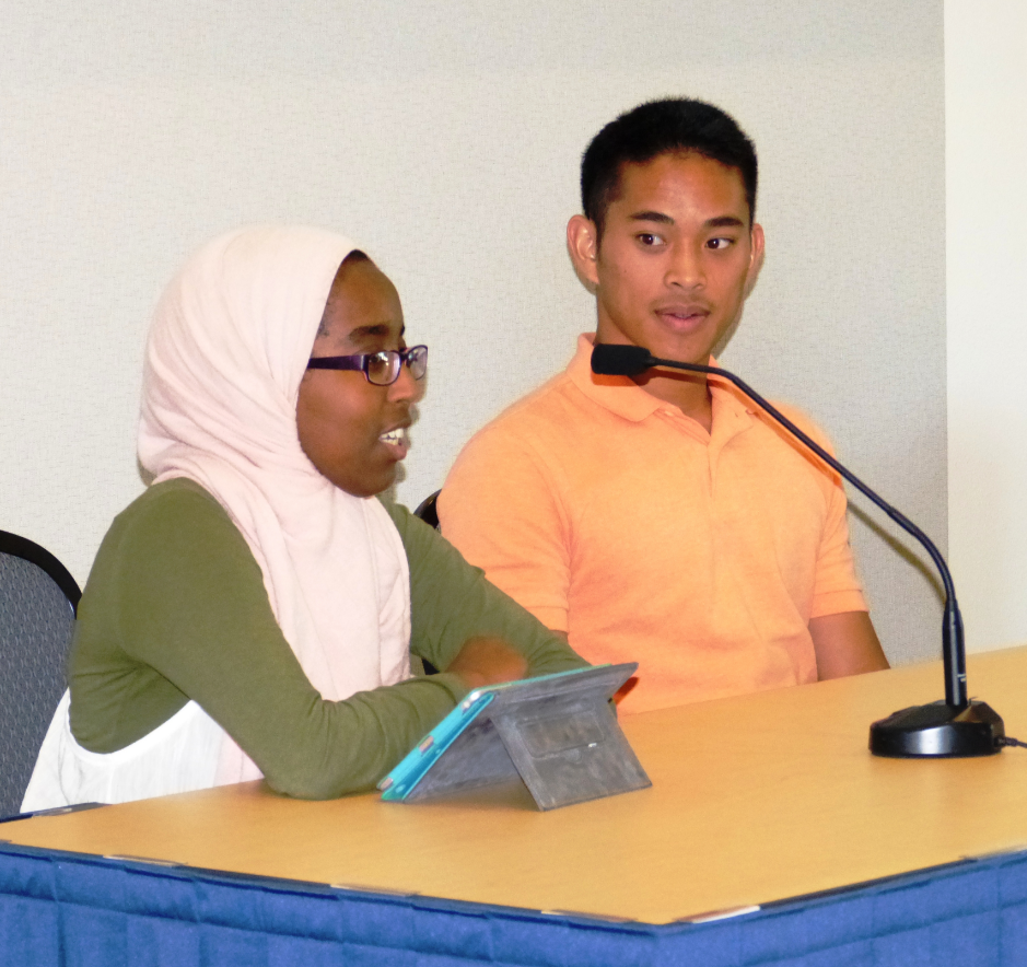 Male and female student sitting at a table. The young woman is speaking