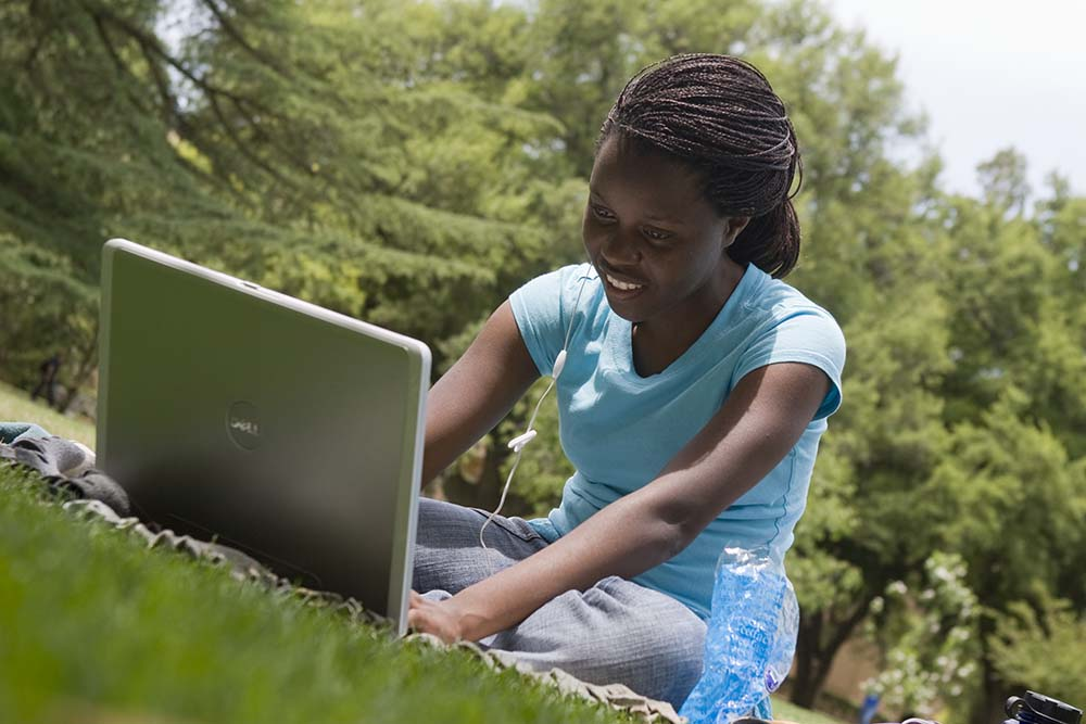 Female student studying in the arboretum with laptop and microphone